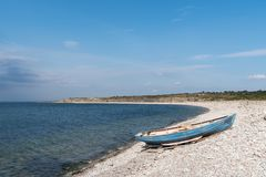 Blue rowing boat by seaside Stock Photo