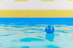 Blue rubber ball floating in the pool.  Stock Images