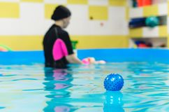 Blue rubber ball floating in the pool.  Royalty Free Stock Image