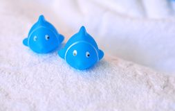 Blue rubber bath toys on a white cotton towel royalty free stock photography