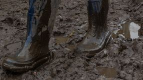 Blue rubber boots covered in dirt. Gait on the mud Royalty Free Stock Photography