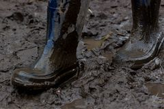 Blue rubber boots covered in dirt. Gait on the mud Royalty Free Stock Image