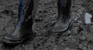 Blue rubber boots in the mud after rain. Close-up. Royalty Free Stock Photos