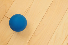 Blue Rubber Racquetball. On Hardwood Court Floor Stock Images