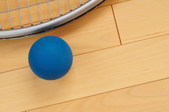 Blue Rubber Racquetball and Racquet. On Hardwood Court Floor Stock Photo