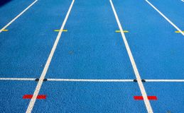 Blue running track with white lines Royalty Free Stock Photos