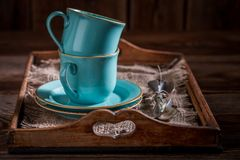 Blue rustic coffee cup and a plate on wooden tray. On old wooden table stock images