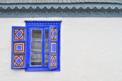 Blue rustic window. Traditional blue window with open shutters on a white wall Royalty Free Stock Photos