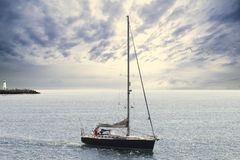 Blue sailboat. Leaving the harbor Stock Photography