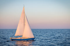 Blue sailboat in the ocean Stock Images