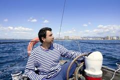 Blue sailor on vintage wooden sailboat ocean sea. Blue sailor man sailing vintage wooden sailboat mediterranean sea Royalty Free Stock Images