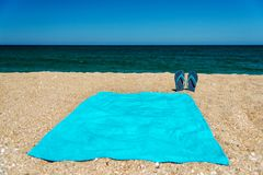 Blue sandal flip flop and towel on yellow sand. Summer fun time and accessories on the beach, summer vacations Stock Photography