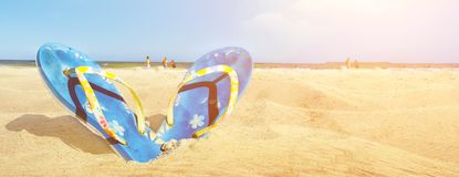 Blue sandal flip flop on the white sand beach with blue sea and sky background in summer vacations copy space. Panoramic view. Blue sandal flip flop on the white royalty free stock images
