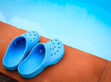 Blue sandals on the poolside Stock Photos