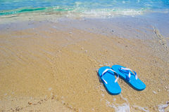 Blue sandals by the shore Stock Photo
