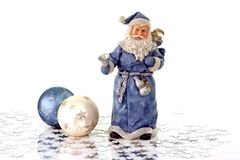 Blue Santa. Claus Figure with two christmas tree balls and silver stars on light Background stock images