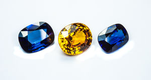 Blue sapphire and topaz. The topaz around with group of the blue sapphires on white background Royalty Free Stock Photo