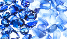 Blue sapphires. Group of blue sapphires and raw gemstones with white background Royalty Free Stock Photo