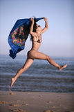 Blue sarong. Woman in bikini jumping with blue scarf Royalty Free Stock Photo