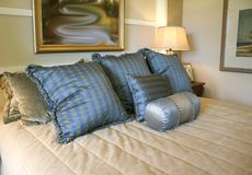 Blue Satin Pillows. On beige quilted bedspread Stock Photo