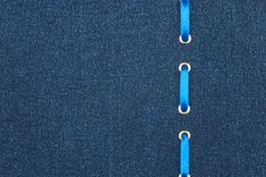 Blue satin ribbon is inserted in a dark denim fabric. View from above. Stock Photography