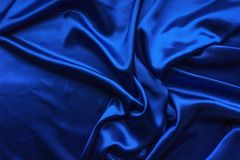 Blue satin, silky fabric, wave, draperies. Beautiful textile backdrop. Close-up. Top view Royalty Free Stock Images