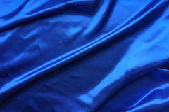 Blue satin, silky fabric, wave, draperies. Beautiful textile backdrop. Close-up. Top view Stock Image
