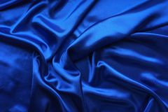 Blue satin, silky fabric, wave, draperies. Beautiful textile backdrop. Close-up. Top view Royalty Free Stock Photos