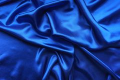 Blue satin, silky fabric, wave, draperies. Beautiful textile backdrop. Close-up. Top view Stock Photo