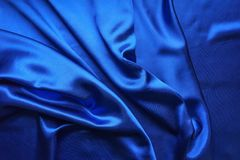 Blue satin, silky fabric, wave, draperies. Beautiful textile backdrop. Close-up. Top view Royalty Free Stock Image