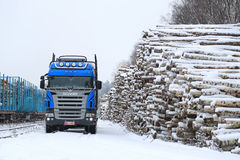 Blue Scania V8 Logging Truck at Snowy Railway Timber Yard Stock Photos