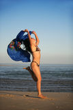 Blue scarf. Woman in bikini jumping with blue scarf Royalty Free Stock Photography
