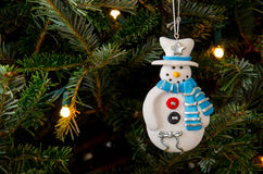 Blue Scarf Snowman Ornament. A clay Christmas ornament in the shape of a snowman wears a white hat and blue and silver scarf royalty free illustration
