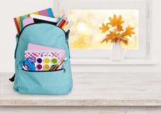 Blue school backpack on wooden table over autumn windowsill background Royalty Free Stock Photography