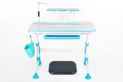 Blue school desk, blue basket, desk lamp and black support under legs Royalty Free Stock Photography