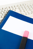 Blue school textbook and computer keyboard Royalty Free Stock Photos