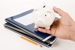Blue school textbook and piggy bank Stock Images