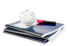 Blue school textbook and piggy bank Royalty Free Stock Image