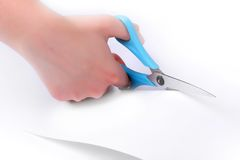 Blue scissors cutting white paper. Royalty Free Stock Photography