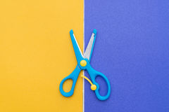 Blue scissors on orange and purple paper. Blue scissors on orange and purple handcraft paper Royalty Free Stock Image