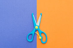 Blue scissors on purple and orange paper. Blue scissors on purple and orange handcraft paper Royalty Free Stock Photography
