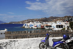 Blue Scooter and Little Venice. Blue scooter parked in front of a fence with a beautiful view of Little Venice, Mykonos, Greece. Image has a shallow depth of Stock Image