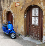 Blue scooter over old wall. Blue scooter parked near old wall Stock Photos