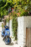 A blue scooter parked at home. Photograph taken at Lefkada Island, Greece. A blue scooter parked in the street. Photograph taken at Lefkada Island, Greece stock photography