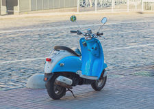 Blue scooter parked on the roadside. Transport Stock Images