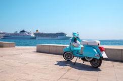 Blue scooter on the waterfront. Blue scooter stands on the waterfront on the background of cruise ships in sunny weather Royalty Free Stock Images