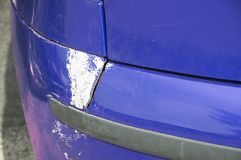 Blue scratched car with damaged paint in crash accident or parking lot and dented damage of metal body from collision.  royalty free stock photos