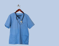Blue scrubs shirt for medical professional hanging on blue wall Royalty Free Stock Photos