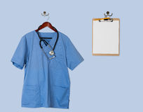 Blue scrubs shirt for medical professional hanging with clipboar Stock Images