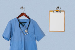 Blue scrubs shirt for medical professional hanging with clipboar Royalty Free Stock Photography